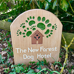 A hand carved sign welcomes visitors to The New Forest Dog Hotel Hampshire home boarding